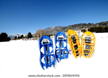 four blue and orange snowshoes in mountains in winter