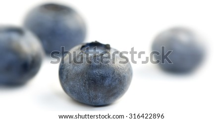 four (4) blueberries shot in extreme close-up the front blueberry sharp and the other three blueberries blurred in the background. - stock photo