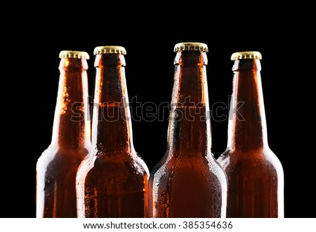 Four bottles of beer on black background - stock photo