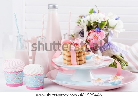 Four bottles of milkshakes, three with straws and glass of milk and plates with cookies, meringues and cloth on white wooden shutter with bouquet from pink tulips and white buttercup