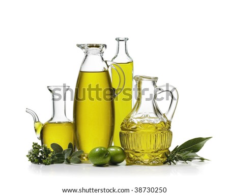 Four bottles of olive oil with two olives and spices on white background - stock photo