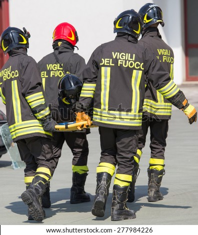 Four brave Firefighters carry a fellow firefighter with the medical stretcher - stock photo