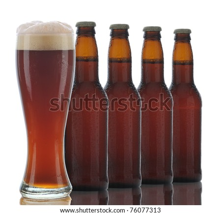 Four Brown Beer Bottles and a Full Glass of dark ale on a white background. - stock photo