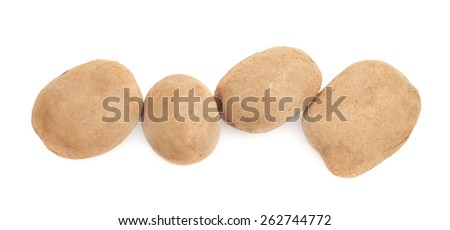 Four brown potatoes lined up in a row, composition isolated over the white background