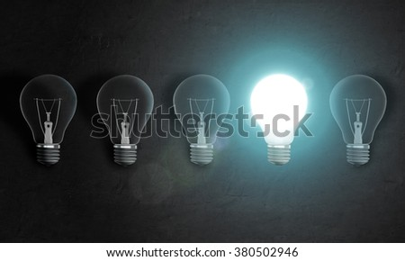 Four bulbs in row on concrete wall, one of them is very bright. Idea concept