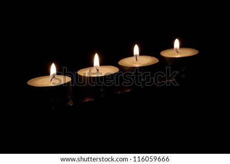 Four burning candles on a black background - stock photo