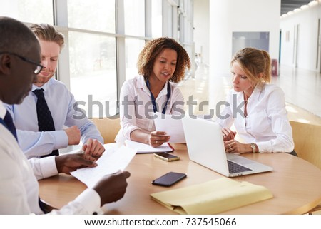 Four business colleagues in a team meeting, close up
