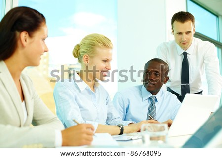 Four business people discussing affairs in office - stock photo