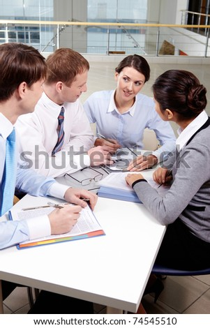 Four business people discussing reports together - stock photo