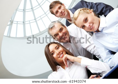 Four business people gathered together - stock photo