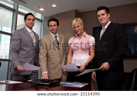 Four business people in a meeting looking at project material - stock photo