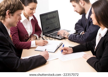 Four business people making notes and typing