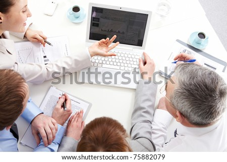 Four business people planning work at meeting - stock photo