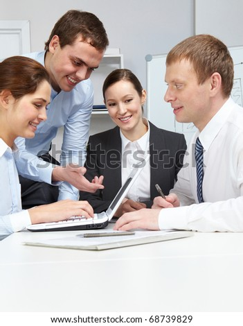Four business people sitting at table, communicating at working with a laptop - stock photo
