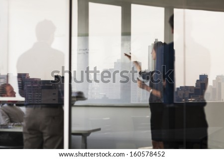 Four business people standing and looking at  white board on the other side of glass wall - stock photo