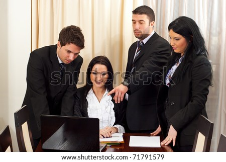 Four business people using a laptop and having a discussion in a meeting room - stock photo