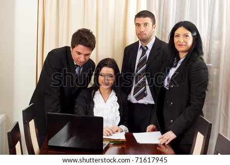Four business people working and looking on laptop in a meeting room - stock photo