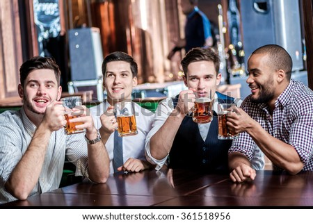 Four businessmen drink beer and enjoyed watching the TV in the bar. Cheerful businessmen friends having fun together in the bar with a beer watching football on TV - stock photo