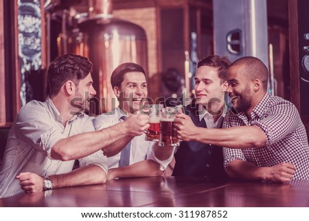 Four businessmen drink beer and rejoice together at the bar. Successful businessmen friends having fun together in the bar with a beer.