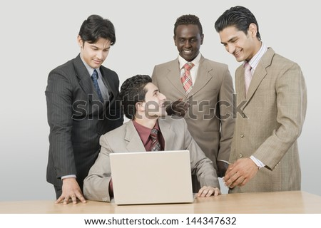 Four businessmen in front of a laptop
