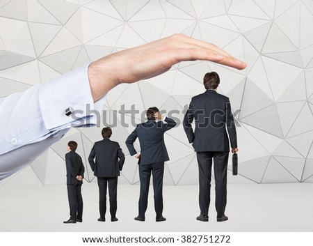 Four businessmen of different size arranged by tallness standing under a huge hand. Grey geometric background. Concept of career growth. - stock photo