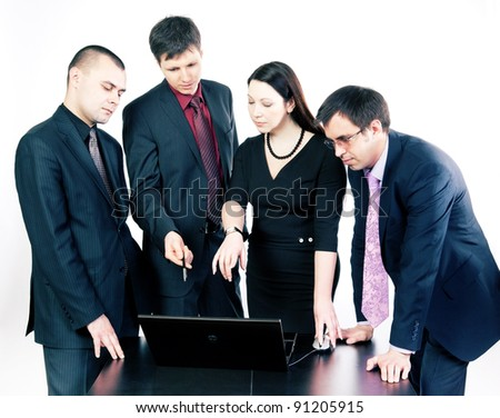 Four businessmen talking on the computer at a meeting in the office