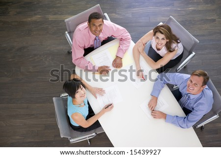 Four businesspeople at boardroom table smiling - stock photo