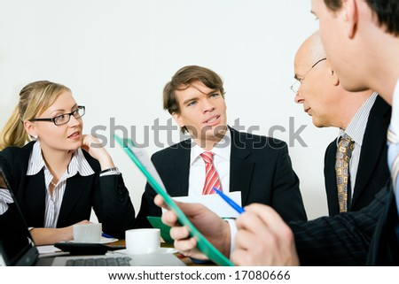 Four businesspeople in a meeting - stock photo