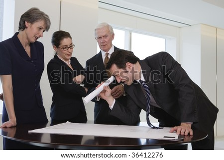 Four businesspeople in an office conference room. - stock photo