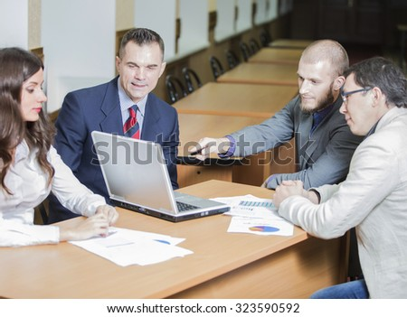 four businesspeople interacting at meeting. beautiful woman with her colleagues