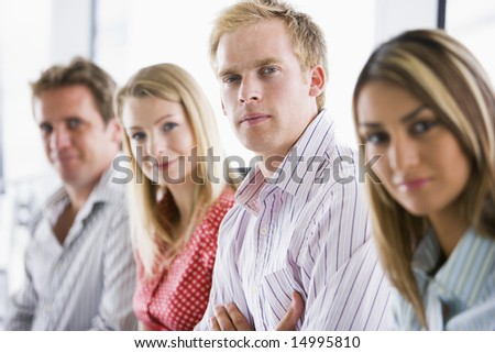 Four businesspeople sitting indoors smiling