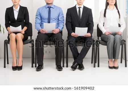 Four candidates competing for one position. Having CV in his hand  - stock photo