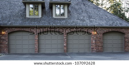 Four Car Garage Doors Made Of Wood And Brick With Trees And Sky In  Background