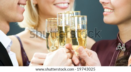Four champagne flutes touching in a toast - stock photo