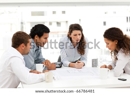 Four charismatic architects looking at plans together around a table - stock photo