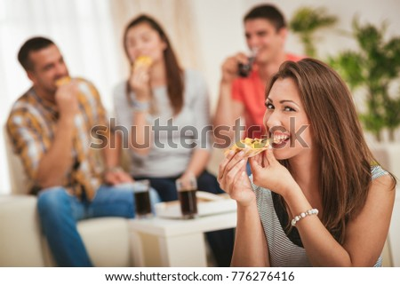 Four cheerful friends hanging out in an apartment. Smiling girl sitting foreground and eating pizza. Selective focus.