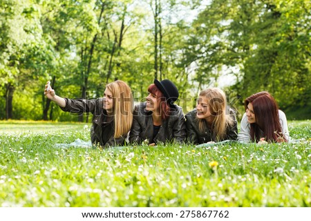 Four cheerful friends lying down in the park and taking photos of themselves with camera. Happy girls taking selfie - stock photo