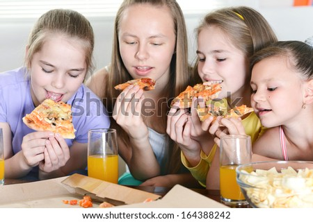 Four cheerful girls watching television together - stock photo