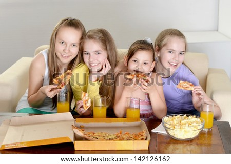 four cheerful girls watching TV together