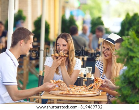 Four cheerful young friends sharing pizza in a outdoor cafe - stock photo