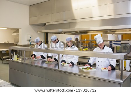 Four Chef's preparing plates in the kitchen
