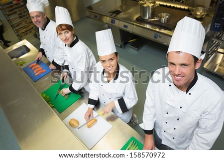 Four chefs preparing food at counter smiling at camera standing in a row in a kitchen