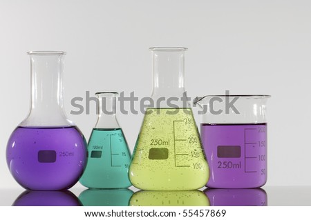 four chemical laboratory flasks with colored liquid