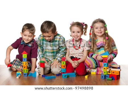 Four children are playing on the floor together; isolated on the white background - stock photo