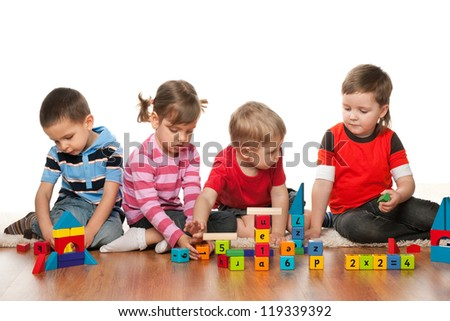 Four children are playing on the floor with blocks - stock photo