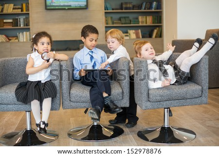 Four children in business clothes having fun in a business center