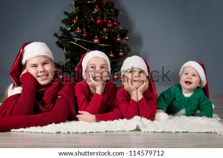 Four children in red hats are around Christmas tree. - stock photo
