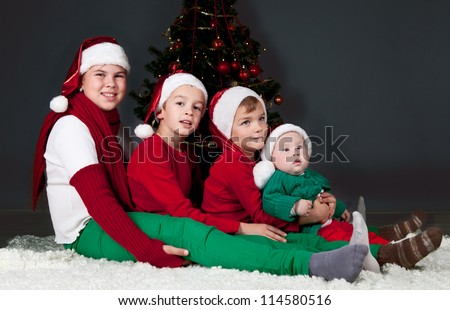 Four children in red hats sitting around Christmas tree. - stock photo
