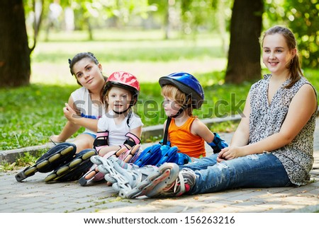 Four children in rollers sit on ground in alley in park