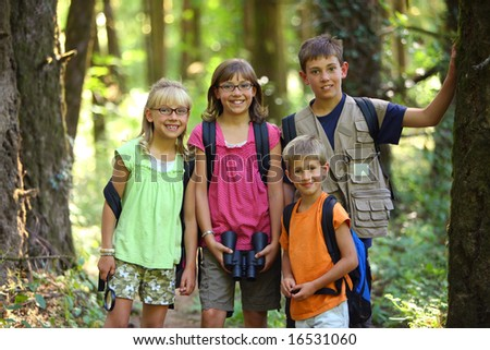 Four children in woods with camping gear - stock photo